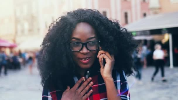 Close up portrait of young exchange student with lush curly hair outside. Beautiful African American girl in plaid shirt stands on street and talking on phone.