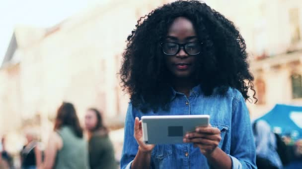 Close up of african american girl standing in city center holding tablet in hands. Beautiful female student in denim shirt walking around the city with digital device. Young woman with curly hair in