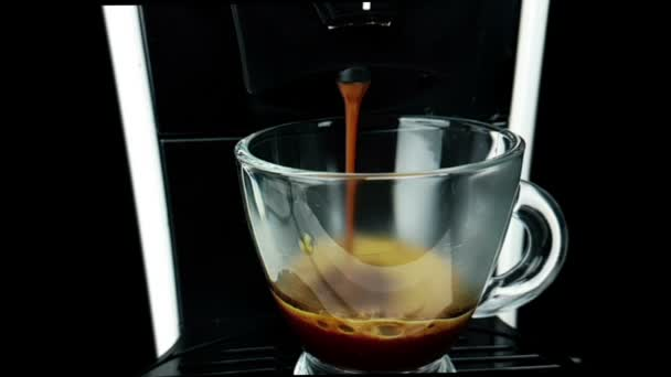 coffee moka machine with hot italian coffee arabica starting go out with foam in slow motion, using a coffee mocha maker machine, breakfast starting concept with a transparent cup of coffee