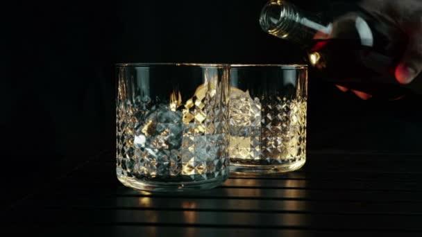 Csapos szakadó whiskey a két szemüveget jégkockát a fa asztal és fekete sötét háttér, jégkocka, whisky összpontosítani pihenni idő a meleg légkört