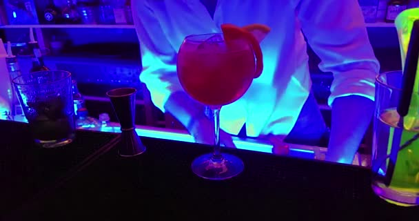 barman prepare red alcohol cocktail drink in the glass with lemon slice on a disco bar table, club atmosphere and fun concept