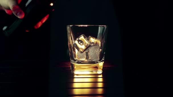 Csapos szakadó whisky az üveg, a jeget a fa asztal és fekete sötét háttér, jégkocka, whisky összpontosítani pihenni idő a meleg légkört
