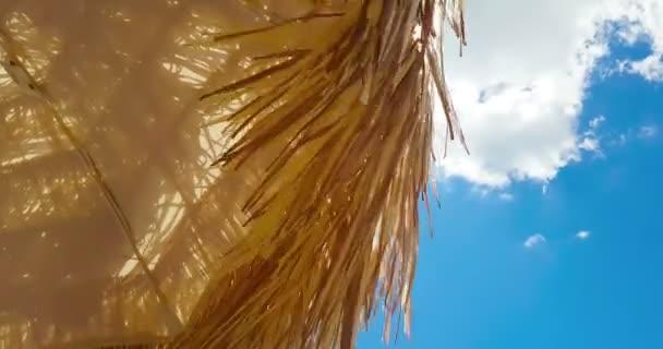 Sonnenschirm aus Stroh unter blauem Himmel, Bewegung auf Wind, Sommerferienreservierung