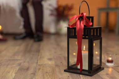 vintage candlestick with ed ribbon on blurred background