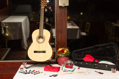 guitar on table with felt-tip pens and bouquet of flowers