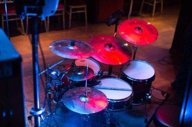 close-up of drum kit and sticks under spotlights