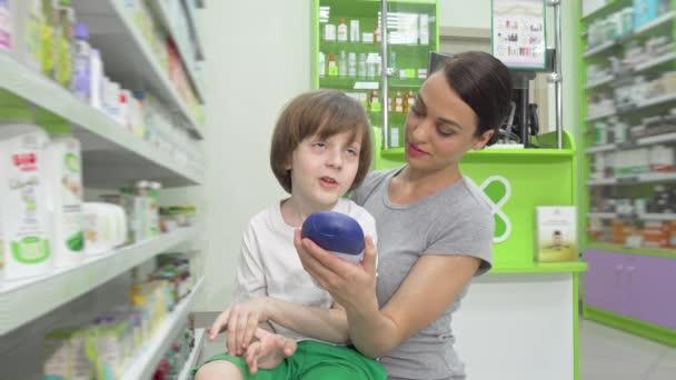 entzückender kleiner Junge im Gespräch mit seiner Mutter beim gemeinsamen Einkaufen in der Drogerie