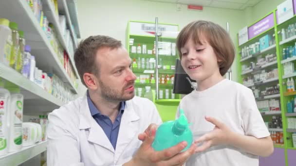 Mature male pharmacist talking to a little boy at drugstore