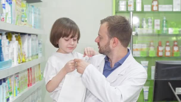 Cheerful pharmacist smiling to the camera with a cute little boy
