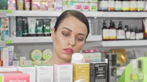 schöne Frau wählt kosmetische Produkte aus dem Regal in der Drogerie