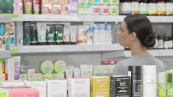 Beautiful woman examining products on sale at local drugstore