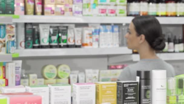 Schöne Frau begutachtet Produkte, die im örtlichen Drogeriemarkt angeboten werden