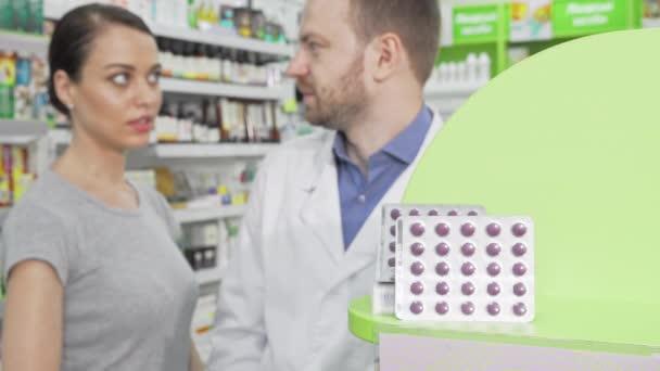 Apotheker bietet seiner Kundin Pillen im Blister an