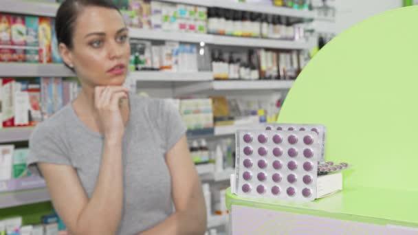 Beautiful woman choosing vitamins at the drugstore