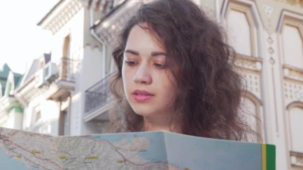 Šťastná mladá žena se usmívá na kameru držící mapu