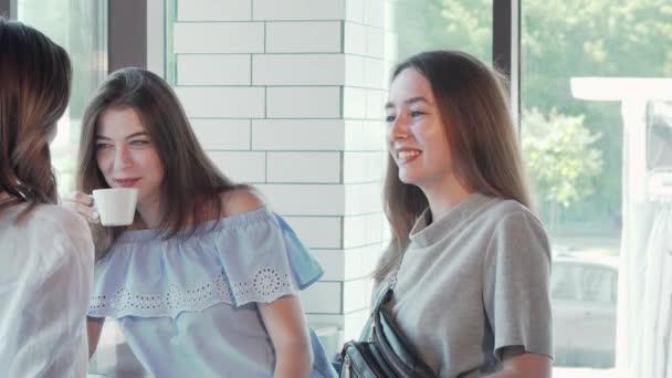 Három szép fiatal nő csevegve miután kávét együtt a kávézóban