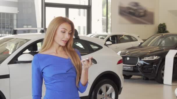 Beautiful happy woman holding car key to her new automobile at the dealership