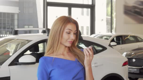 Happy female driver showing car key to the camera after buying new auto
