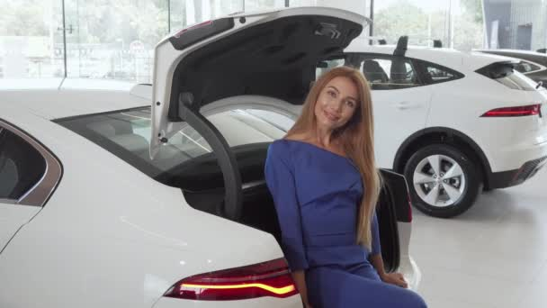 Krásná šťastná žena, která sedí v otevřeném kufru svého nového auta u dealerství