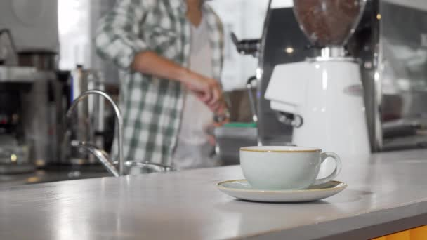Coffee cup on the counter barista working at the coffee shop on background