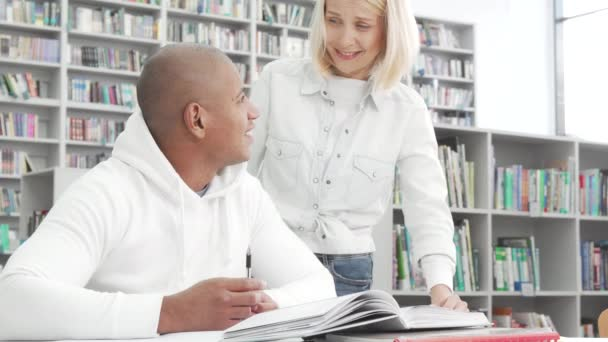 Lovely college couple chatting while studying at the library