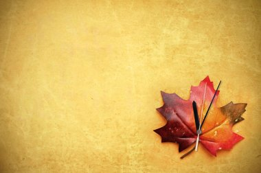 Autumn maple leaf with clock hand