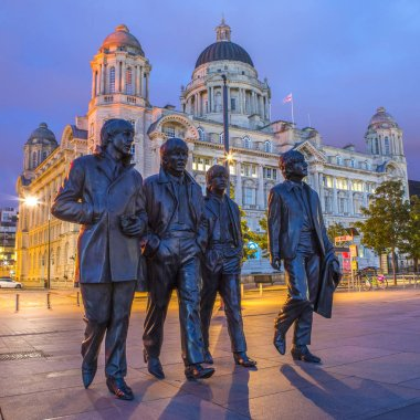 LIVERPOOL, UK - JULY 29TH 2018: Statues of The Beatles - Paul, George, Ringo and John on Pier Head in Liverpool, UK, with the Port of Liverpool building in the background, on 29th July 2018.