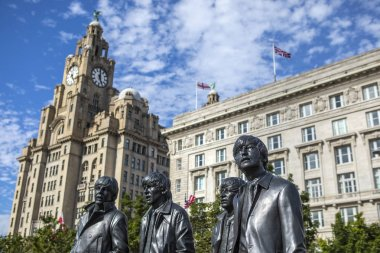 Liverpool, UK - July 30th 2018: The statue of The Beatles - John, Ringo, George and Paul, with the historic Royal Liver Building and Cunard Building in the background, in the city of Liverpool, on 30th July 2018.