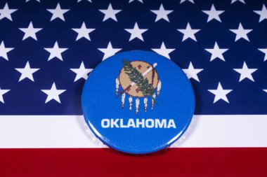 London, UK - November 15th 2018: The symbol of the state of Oklahoma, pictured over the flag of the United States of America.