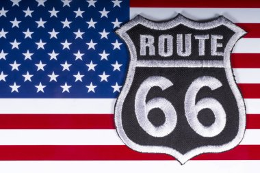 London, UK - November 20th 2018: The Route 66 logo, pictured over the flag of the United States of America.