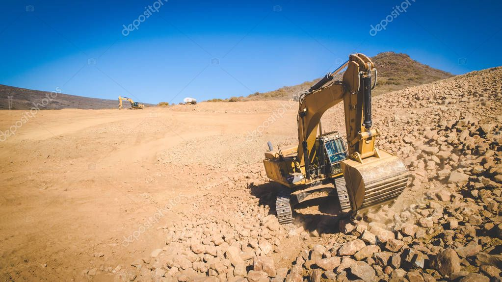 big excavator digging out gravel and rocks on a dig site