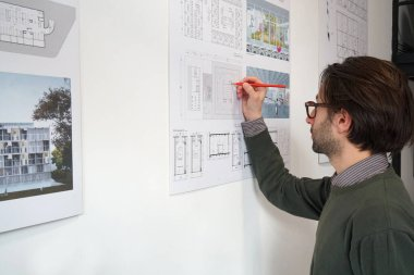 Young architect man with casual wear notes in his construction plan