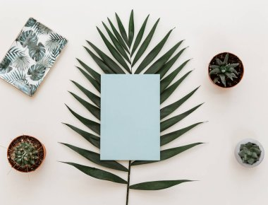 Flat lay summer composition. Creative concept tropical leaves and invitation cards. Top view, copy space