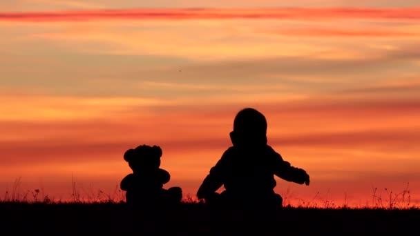 Baby a teddy bear hračky siluetu sedící na trávě a podívejte se na nebe