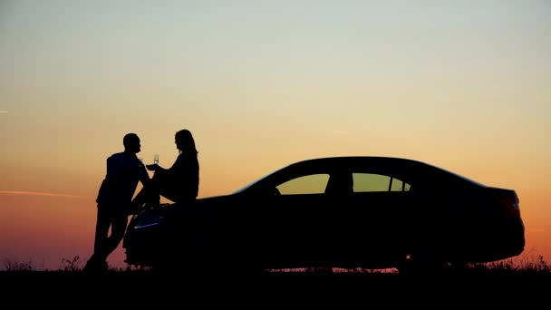 Pár szerelmesek silhouette ital pezsgő, a naplemente, a nő ül, autó, romantikus