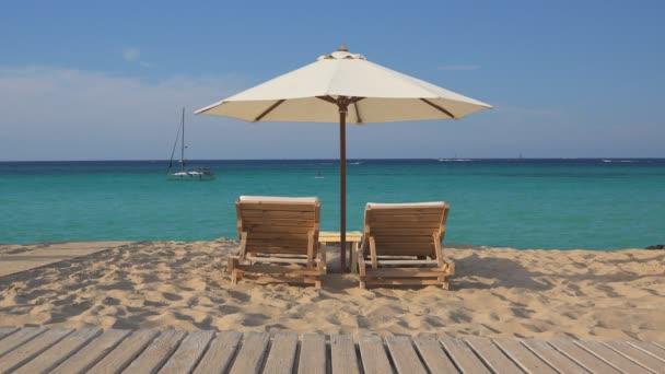 Tropických exotických pláž s dvěma lehátky prázdné dřevěné salonek a bílý deštník