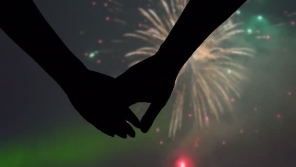Detail silhouettes of hands joining during night fireworks celebration