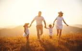 Šťastná rodina: matka, otec, děti syn a dcera na přírodu na západ slunce