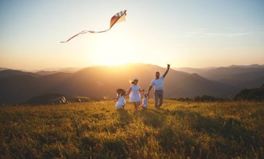 Happy family father,  mother and children launch a kite on nature at sunset