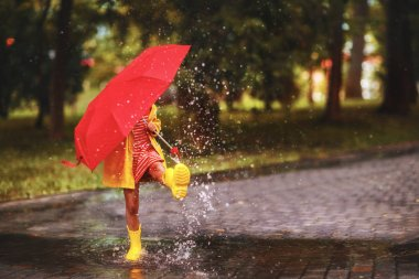 happy child girl with an umbrella and rubber boots in puddle on an autumn wal