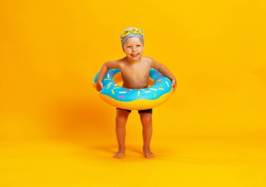 happy child boy in swimsuit with swimming ring donut on a colored yellow backgroun