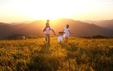 Happy family: mother, father, children son and  daughter on nature  on sunse