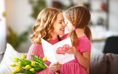 happy mother's day! child daughter congratulates mother and gives a bouquet of flowers to tulips and postcar