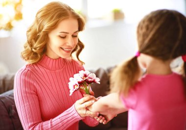 happy mother's day! child daughter congratulates mother and gives a bouquet of flowers and postcar