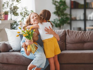 Happy mother's day! Children congratulates moms and gives her a gift and flowers tulip