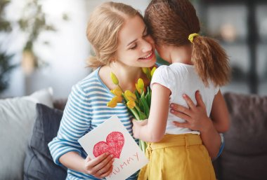 Happy mother's day! Child daughter congratulates moms and gives her a postcard  and yellow flowers  tulip