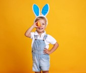 Photo funny happy child boy with easter eggs and bunny ears on yellow