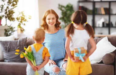 Happy mother's day! Children congratulates moms and gives her a