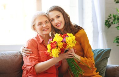Happy mother's day! adult daughter gives flowers and congratulat