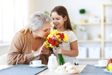 Happy mother's day! granddaughter gives flowers and congratulate